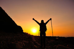 Hiking woman raised arms to sunrise Stock Photos