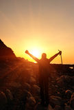 Hiking woman raised arms to sunrise Royalty Free Stock Images