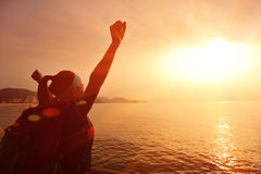 Hiking woman raised arms to sunrise Stock Images