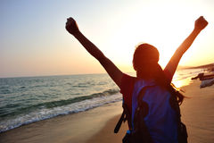 Hiking woman raised arms to sunrise. At seaside Royalty Free Stock Photo
