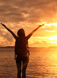 Hiking woman raised arms to sunrise Stock Photo