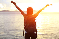 Hiking woman raised arms to sunrise Royalty Free Stock Image