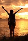Hiking woman raised arms to sunrise Stock Photos