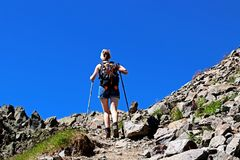 Hiking woman reaching goal on a trail near Chamonix. Trekker lady in action with motivation courage and perseverance under the hot summer sun and reaching goal stock images