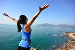 Hiking woman seaside with arms open Stock Image