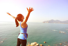 Hiking woman seaside with arms open Stock Photos