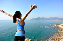 Hiking woman seaside with arms open Royalty Free Stock Photo
