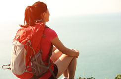 Hiking woman sit seaside rock Royalty Free Stock Images