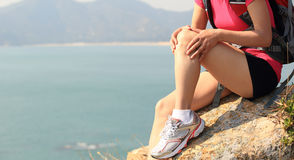 Hiking woman sit seaside rock. And looking her broken knee Stock Image