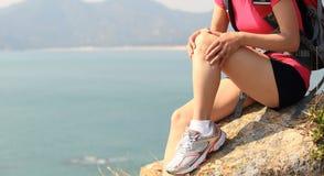 Hiking woman sit seaside rock Stock Image