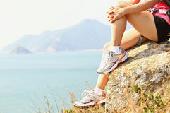 Hiking woman sit seaside rock Royalty Free Stock Image