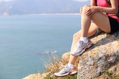 Hiking woman sit seaside rock Stock Photography
