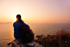 Hiking woman sit at sunrise seaside Stock Image