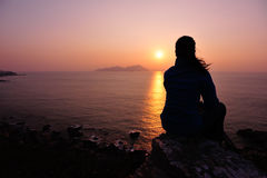 Hiking woman sit at sunrise seaside Stock Images