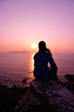 Hiking woman sit at sunrise seaside. Hiking woman sit on mountain rock looking the sunrise at the sea Stock Photos