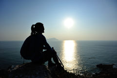 Hiking woman sit at sunrise seaside Stock Image