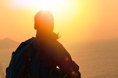 Hiking woman sit at sunrise seaside Royalty Free Stock Images