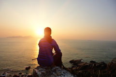 Hiking woman sit at sunrise seaside. Hiking woman sit on mountain rock looking the sunrise at the sea Royalty Free Stock Photography