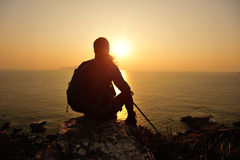 Hiking woman sit at sunrise seaside Stock Photography