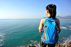 Hiking woman stand seaside rock Royalty Free Stock Photos