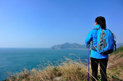 Hiking woman stand seaside rock Stock Photography