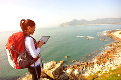 Hiking woman stand seaside use digital tablet. Hiking woman stand on seaside rock and use digital tablet Stock Photography