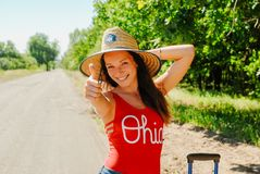 Hiking woman in a straw hat and red shirt giving thumbs up smiling. woman hiker smiling joyful at camera stock photo