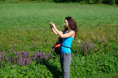 Hiking woman take photos with her smart phone Royalty Free Stock Photos