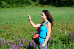Hiking woman take photos with her smart phone Stock Image