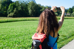 Hiking woman take photos with her smart phone Royalty Free Stock Images