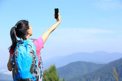Hiking woman taking photo with phone Stock Images