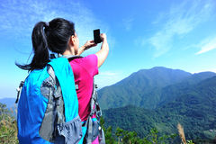 Hiking woman taking photo with phone Royalty Free Stock Photography