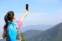 Hiking woman taking photo with phone. Hiking woman taking self photo with phone at mountain peak Stock Photography
