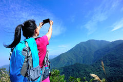 Hiking woman taking photo with phone Royalty Free Stock Images