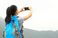 Hiking woman taking photo with phone. Hiking woman taking photo with smart phone at mountain peak Royalty Free Stock Images