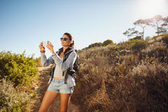Hiking woman taking photo with smart phone Stock Photography