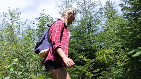 Hiking woman trekking in forest with backpack and eating wild raspberries stock footage