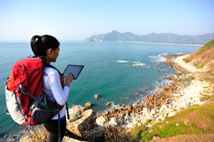 Hiking woman use digital tablet. Hiking woman stand on seaside rock and use digital tablet Royalty Free Stock Images