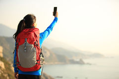 Hiking woman use smart phone taking photo Royalty Free Stock Photo