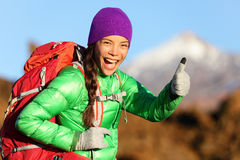Hiking woman in winter jacket giving thumbs up. Smiling. Young Asian woman hiker smiling joyful at camera outdoor on hike trip. Beautiful young mixed race Asian Stock Photo