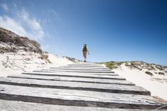 Hiking woman in white sand dunes on her way to the beach royalty free stock photography