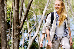 Hiking in woods. Women walking outdoor in the woods, happy exploring and adventure lies ahead for these wilderness trekking friends royalty free stock photo