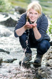 A hiking young blond woman refreshes itself in to a brook Royalty Free Stock Photos