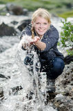A hiking young blond woman refreshes itself in to a brook Royalty Free Stock Image
