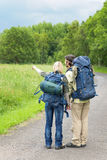 Hiking young couple backpack asphalt Royalty Free Stock Photos