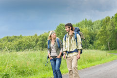 Hiking young couple backpack asphalt road country Royalty Free Stock Images