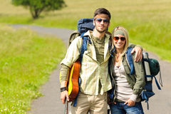 Hiking young couple backpack tramping asphalt road Stock Photo