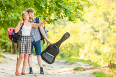 Hiking young couple with guitar backpack outdoor Royalty Free Stock Images