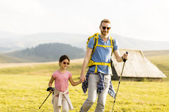 Hiking. Young father and daughter enjoy hiking on a sunny day royalty free stock image