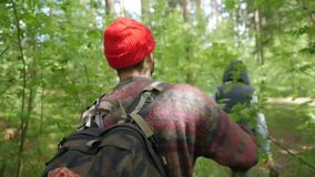 Hiking Young Man Trekking in Forest. Rear back view of hiker walking on trek with backpack through green park. Caucasian stock footage